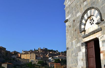 The Romanesque Church of San Giovanni and the Medieval tow of Campiglia Marittima in the background.